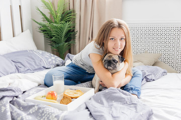 Young woman with her dog in a bed. Breakfast in bed