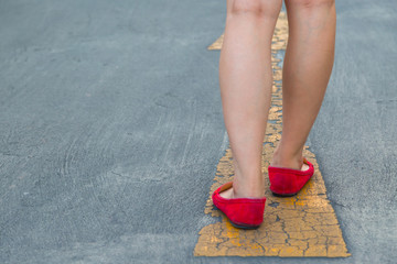 Girl wear red shoes  walking towards with yellow traffic arrow signage on an asphalt road