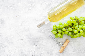 Fototapete - Open the wine concept. White wine in glass bottle near bunch of grapes and corkscrew on grey background top view copy space