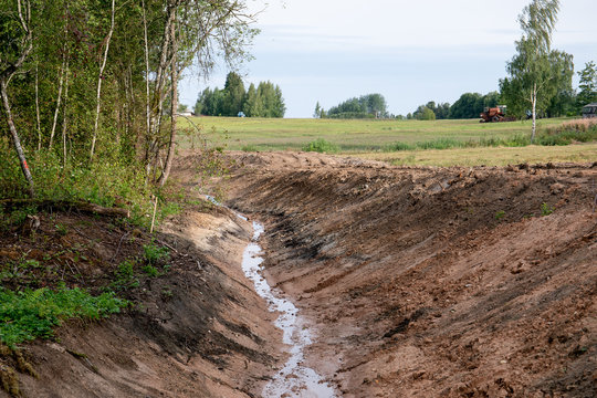 system of drainage ditch in the woods for water colleting, green trees around