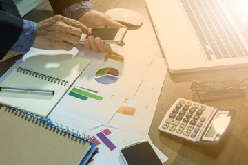 Business documents on office table with laptop, smart phone  and graph financial and man working in the background. Business concept.