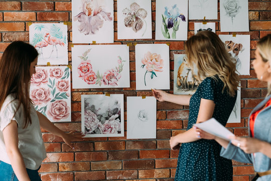 painting courses artwork. creative workshop decor. painting hobby and leisure concept. beautiful watercolor pictures of flowers and animals on the wall. students looking at drawings