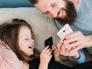 happy family leisure and gratifying rewarding fatherhood. dad and daughter sharing a laugh together after seeing a funny pic or video online. father and kid using mobile phone.