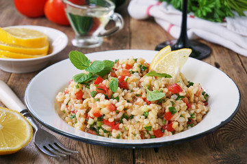 Salad with bulgur, tomatoes, cucumbers and fresh herbs