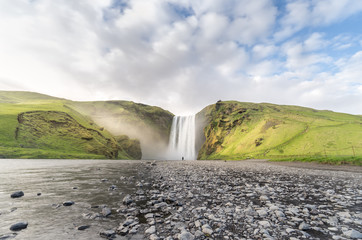 A lone person stands in front of the mighty waterfall Skogafoss, as the sunset light plays across the mountains and spray from the vibrant summer scene in Iceland.