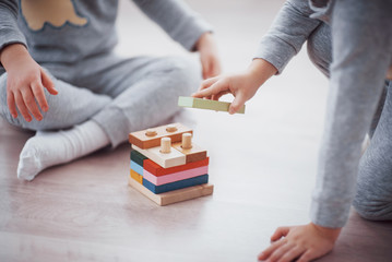 Obraz Children play with a toy designer on the floor of the children's room. Two kids playing with colorful blocks. Kindergarten educational games - fototapety do salonu