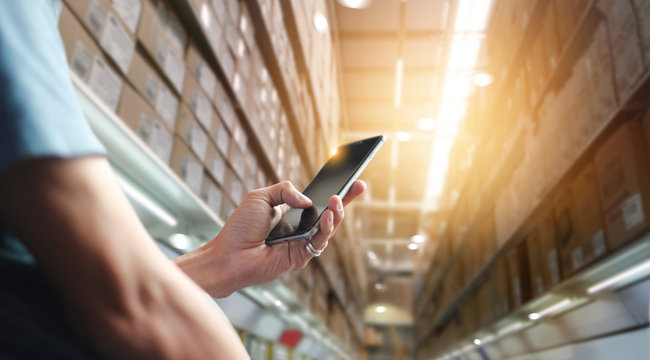 Factory worker using application on mobile smartphone to operate automation for modern trade. Checking order in large warehouse. Import and export the shipping cargo. Business marketing and technology