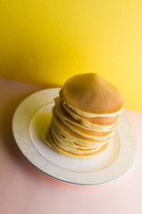 Pancakes on a yellow pink background. Many pancakes on a white plate with copy space. Delicious...