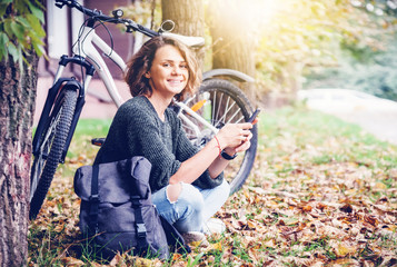 Beautiful young smiling girl woman with mobile phone in hands sits in autumn park on grass next to her bicycle