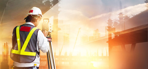 Double Exposure, Surveyor builder and engineer working with theodolite transit equipment at construction site outdoors in the city sunset background.