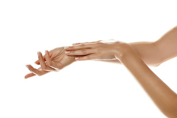 closeup of female hands applying hand cream on white background