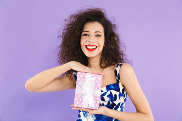 Portrait of a cheerful young woman holding present box