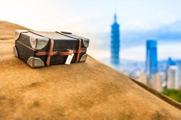 Travel To Taipei / Taiwan travel scene: miniature suitcase at top of yellow stony mountain, Taipei city skyline at the background (copy space)