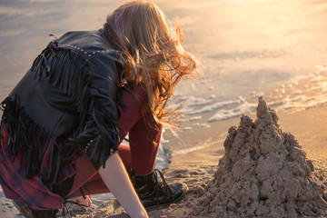 Young woman building and making sand castle next to sea. Calm, relaxing and romantic evening during sunset at the beach side. Remembering the childhood. Loneliness concept.