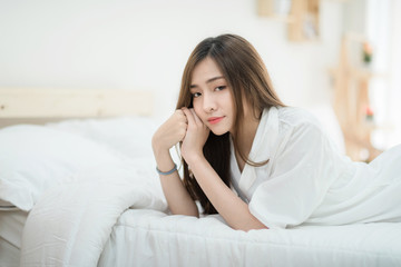 A beautiful young woman lying in bed comfortably and happily. Happy morning. Portrait of a smiling pretty  girl relaxing in white bed.