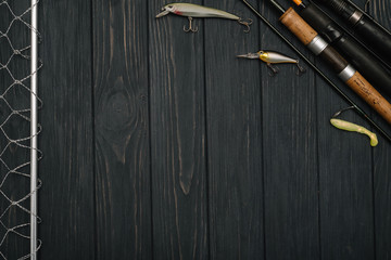 Fishing tackle - fishing spinning, hooks and lures on darken wooden background. Top view.