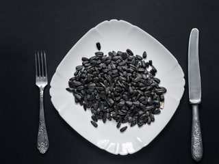 Sunflower seeds lie on a white plate on a black background