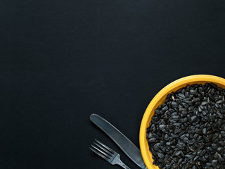 Sunflower seeds on a yellow plate and knife with a fork in the lower right corner of the frame on a black background