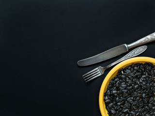 Yellow plate with sunflower seeds and tableware over a plate on a dark background