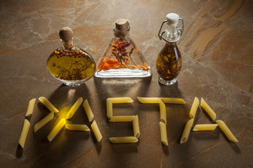 """Bottles extra virgin olive oil with spices and inscription """"pasta"""" on a ceramic background"""