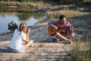 Man and woman by the lake with guitar and photo camera.