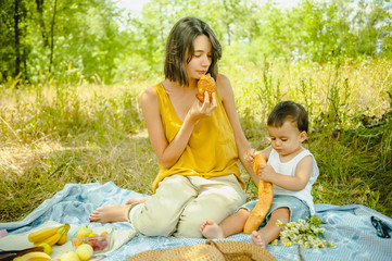 mother and son eating croissant and baguette at picnic in field