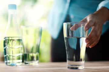 Hand touching and reaching for the glass of drinking water on wooden table, green nature background. Healthy concept