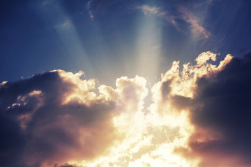 Beautiful bright colorful stunning sunset sky, sun rays in the clouds