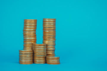 Columns of coins, piles of coins on blue background, business and financial concept.