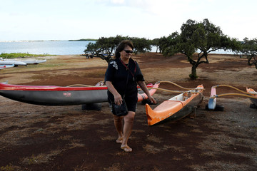 Lane Endo of the Alapahoe outrigger canoe club checks their canoes after moving them off the beach to higher ground as Hurricane Lane approaches Honolulu