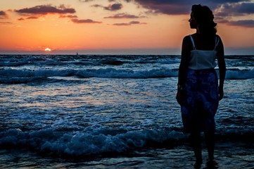 The silhouette of a beautiful young woman in a long light dress entering the sea during the tide at the sunset.