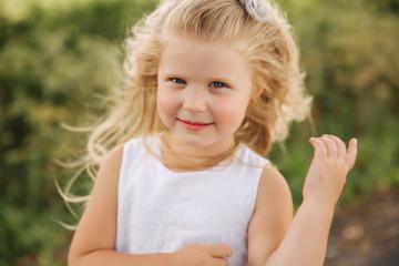 Portrait of smiling little daughter outdoors. Blonde hair little girl