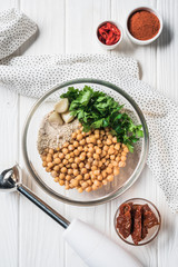 Flat lay with chickpeas and other ingredients for hummus in bowl, blender and dried tomatoes on wooden tabletop
