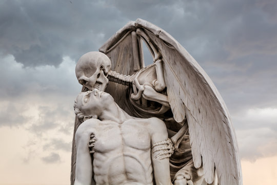 The Kiss of Death statue in Poblenou Cemetery in Barcelona. This marble sculpture depicts death, as a winged skeleton, kissing a handsome young man. The sculpture is at once romantic and horrifying.