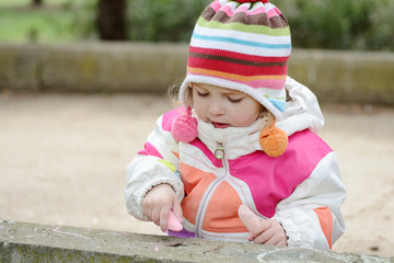 toddler girl drawing with chalk