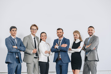 smiling businesspeople with crossed arms posing near board after training in hub