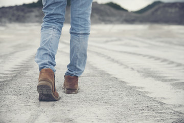 Picture of feet of person back view (lonely girl),wearing brown leather boots and blue jeans.Foot of traveler Walk toward successful on path way and green fields beside.Travel and success concept