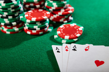Poker chips and playing cards on green felt table. Casino concept.