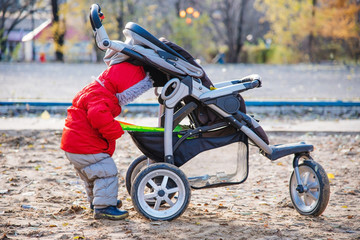 a small child takes his toys out of the stroller