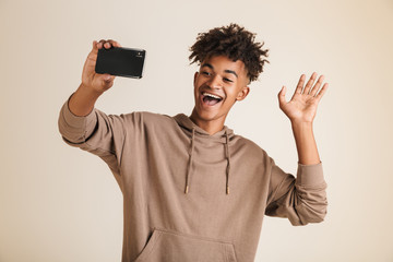American man dressed in hoodie taking a selfie isolated while waving.
