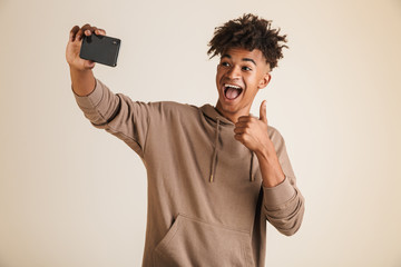 Afro american man dressed in hoodie taking a selfie isolated while showing thumbs up gesture.