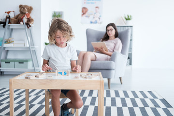 Boy sitting at the table and playing with blocks while his counselor is taking notes