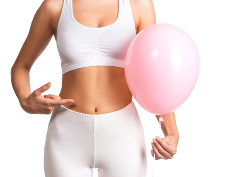 Woman holding a balloon, feeling bloated concept