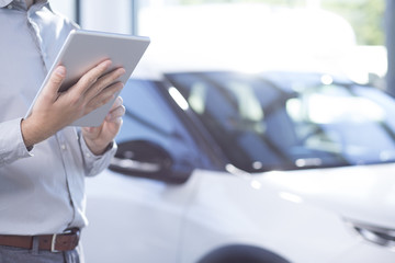 Close-up of professional car dealer with tablet in the exclusive showroom