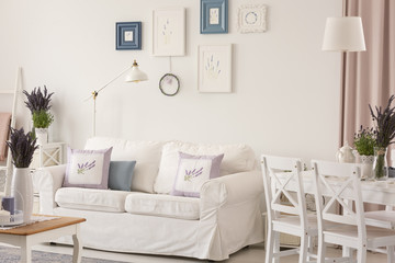 White room interior with couch with pillows, posters on wall, dining table with chairs and fresh lavender in the real photo