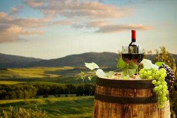 Wall Mural - Red wine bottle and wine glass on wodden barrel. Beautiful Tuscany background