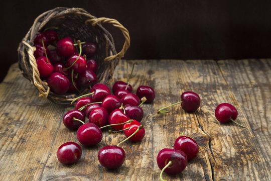 Wicker basket of cherries on wood