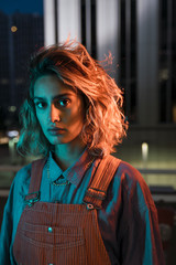 Young woman wearing overalls at night