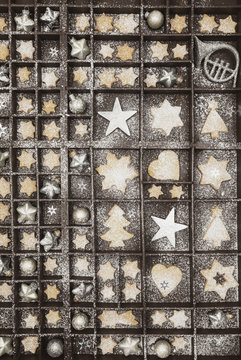 Homemade Christmas cookies, stars and Christmas baubles in old wooden type case