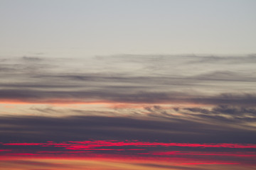 Sky clouds background. Cumulus pink red clouds in the sunset. Color clouds in the evening. Sky with a pastel colored background